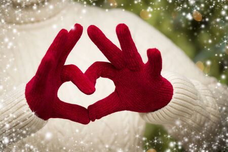 red gloves: Woman in Sweater with Seasonal Red Mittens Holding Out a Heart Sign with Her Hands with Snow Flakes Border.