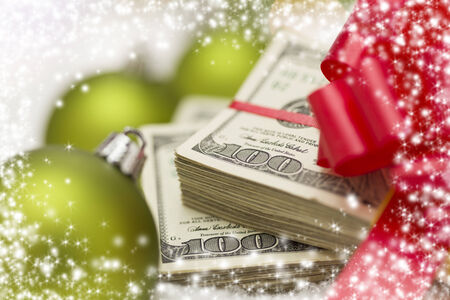 christmas profits: Stack of One Hundred Dollar Bills with Red Bow Near Green Christmas Ornaments on Snow Flakes with Snow Flake Border.