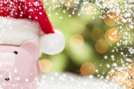 gifting: Pink Piggy Bank vestida de rojo y blanco Gorro de Pap� Noel en copos de nieve con Extracto verde y oro de la nieve y luz de fondo - habitaci�n para su propio texto. Foto de archivo