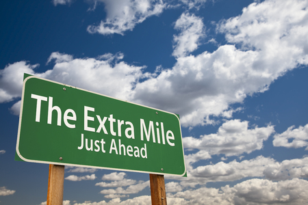 just ahead: The Extra Mile Just Ahead Green Road Sign Over Dramatic Clouds and Sky.
