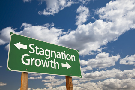stagnate: Stagnation or Growth Green Road Sign Over Dramatic Clouds and Sky.