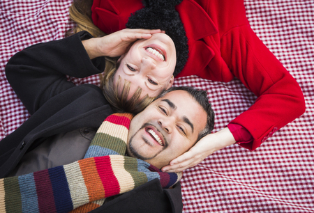 Young Mixed Race Couple Wearing Winter Clothing on Blanket in Park  photo