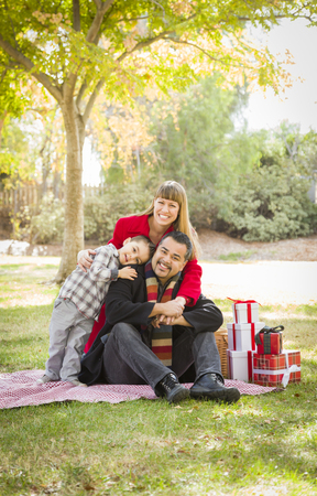 mixed family: Young Mixed Race Family Enjoying Christmas Gifts in the Park Together