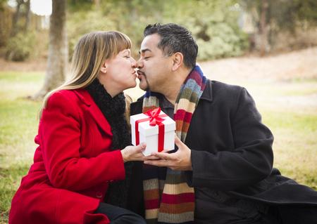mixed race couple: Joven Atractiva pareja de raza mixta Sharing Navidad o D�a de San Valent�n de regalo en el parque Foto de archivo