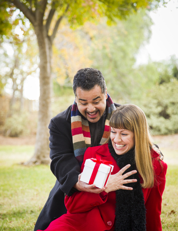 Young Attractive Mixed Race Couple Sharing Christmas or Valentines Day Gift in the Park  photo