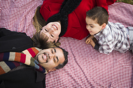 Young Mixed Race Family in Winter Clothing Laying on Their Backs on Picnic Blanket in the Park Together  photo