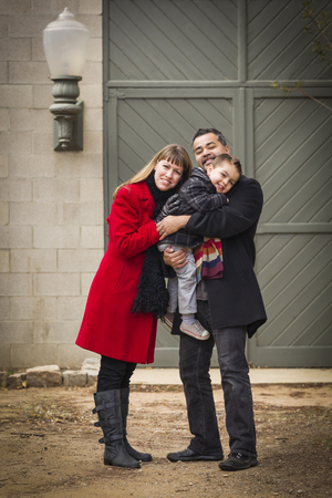 Young Mixed Race Couple in Winter Clothing Hugging and Kissing Son in Front of Rustic Building Together  photo