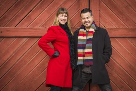 mixed race couple: Joven de la raza mezclada Retrato de pareja en ropa de invierno contra la puerta de granero