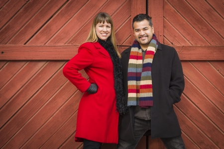 Young Mixed Race Couple Portrait in Winter Clothing Against Barn Door  photo