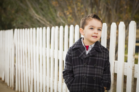 Young Mixed Race Boy Waiting For School Bus Along Fence Outside  photo
