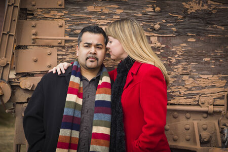 Young Mixed Race Couple Portrait in Winter Clothing Against Side of Rustic Train  photo