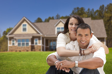 Young Happy Hispanic Young Couple in Front of Their New Home. Stock Photo