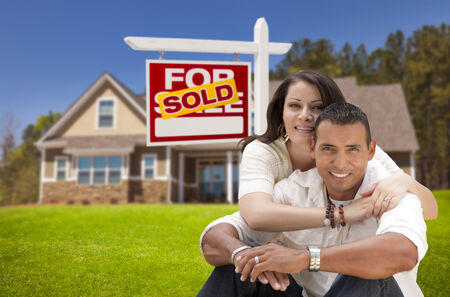 Young Happy Hispanic Young Couple in Front of Their New Home and Sold For Sale Real Estate Sign. photo