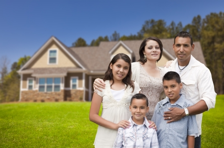 Happy Young Hispanic Family in Front of Their New Home. Banque d'images