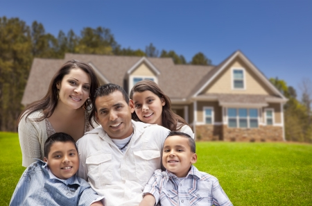 Happy Young Hispanic Family in Front of Their New Home. Stock Photo