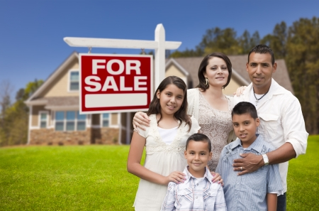 Young Happy Hispanic Young Family in Front of Their New Home and For Sale Real Estate Sign. photo