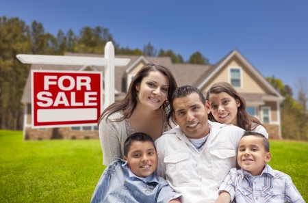этнический: Молодой счастливый молодой семьи Испанец в передней части их новый дом и для продажи недвижимости знак. Фото со стока