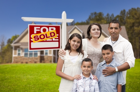 Young Happy Hispanic Young Family in Front of Their New Home and Sold For Sale Real Estate Sign. photo