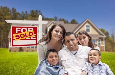 sales person: Young Happy Hispanic Young Family in Front of Their New Home and Sold For Sale Real Estate Sign.