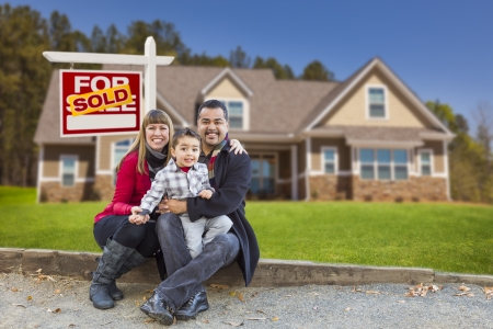Happy Mixed Race Family in Front of Their New Home and a Sold For Sale Real Estate Sign. photo