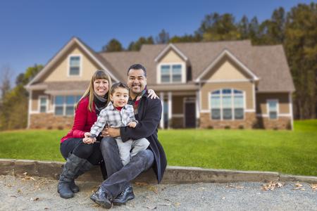 Gelukkig Mixed Race familie voor hun mooie nieuwe woning. Stockfoto