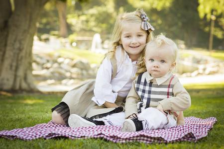 picnic blanket: Ni�a dulce que se sienta con su hermano del beb� en una manta de picnic al aire libre en el parque.