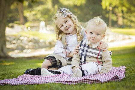 picnic blanket: Dulce ni�a abraza a su beb� Brother en una manta de picnic al aire libre en el parque. Foto de archivo