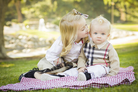 Sweet Little Girl Kisses Her Baby Brother on His Cheek Outdoors at the Park.  photo