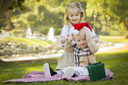 reluctant: Sweet Little Girl Tries to Put A Santa Hat On Her Reluctant Baby Brother Outdoors at the Park.  Stock Photo