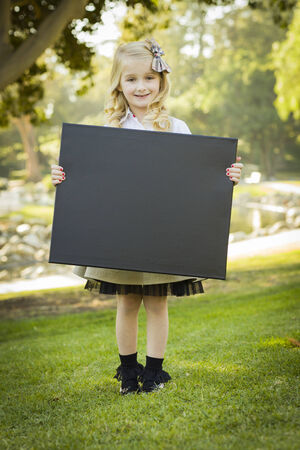 Cute Little Blonde Girl with a Bow in Her Hair Holding a Black Chalkboard Outdoors.  photo