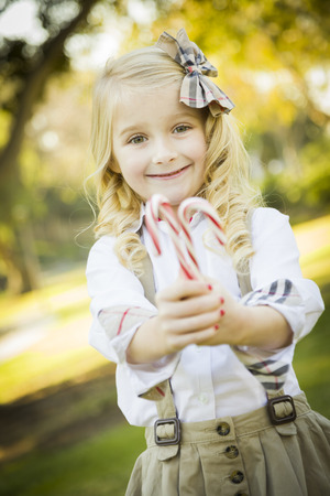 hair bow: Cute Little Girl with a Bow in Her Hair Holding Her Christmas Candy Canes Outdoors.