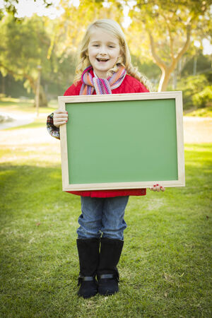 Cute Little Blonde Wearing Winter Coat and Scarf Holding a Green Chalkboard Outdoors.  photo