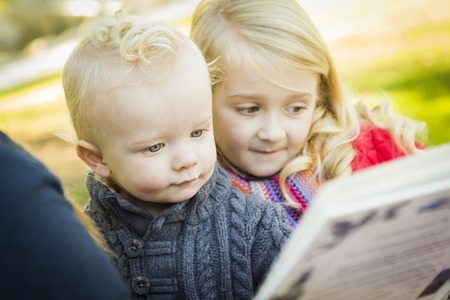 single parent: Mother Reading a Book to Her Two Adorable Blonde Children Wearing Winter Coats Outdoors.  Stock Photo
