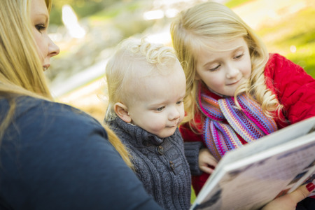 Mother Reading a Book to Her Two Adorable Blonde Children Wearing Winter Coats Outdoors.  photo
