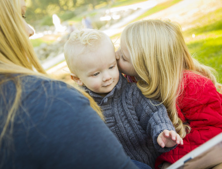 blue eyed: Mother Reading a Book to Her Two Adorable Blonde Children Wearing Winter Coats Outdoors.  Stock Photo