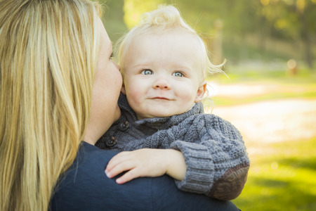 blue eyed: Mother Embracing Her Adorable Blonde Haired Blue Eyed Baby Boy Outdoors.