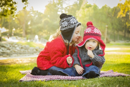 Little Girl Whispers A Secret to Her Baby Brother Wearing Winter Coats and Hats Sitting Outdoors at the Park.  photo