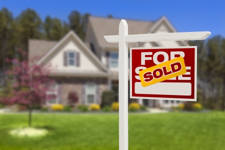 first move: Sold Home For Sale Real Estate Sign in Front of Beautiful New House. Stock Photo