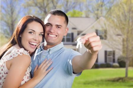 Mixed Race Opgewonden Militaire paar voor New Home pronken met hun huissleutels.