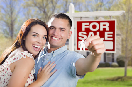 Mixed Race Excited Military Couple In Front of New Home with New House Keys and For Sale Real Estate Sign Outside. photo