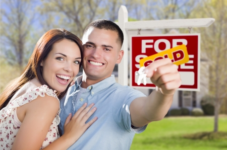 Mixed Race Excited Military Couple In Front of New Home with New House Keys and Sold Real Estate Sign Outside. Stock Photo