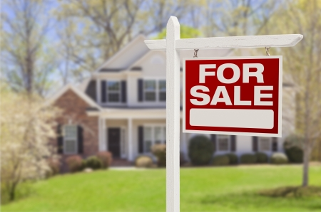 front house: Home For Sale Real Estate Sign in Front of Beautiful New House. Stock Photo