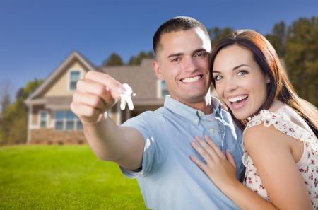 pareja en casa: Mestizo, emocionado Pareja militar frente a la nueva casa mostrando sus llaves de la casa. Foto de archivo