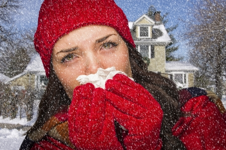 miserable: Miserable Sick Woman In Falling Snow Blowing Her Sore Nose With Tissue Outside. Stock Photo