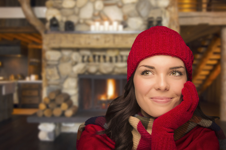 Smiling, Comfortable Mixed Race Girl Looking To The Side Enjoying Warm Fireplace In Rustic Cabin.