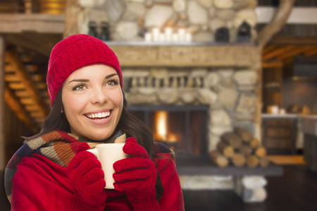 red chilly: Smiling Mixed Race Girl Looking to The Side Enjoying a Warm Fireplace and Holding Mug of Cocoa or Hot Tea. Stock Photo