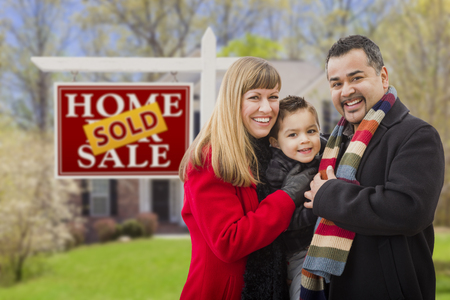 Warmly Dressed Young Mixed Race Family in Front of Sold Home For Sale Real Estate Sign and House. photo