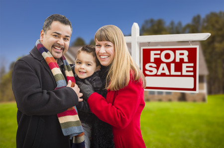warmly: Warmly Dressed Young Mixed Race Family in Front of Home For Sale Real Estate Sign and House. Stock Photo