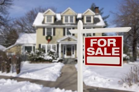 雪の中で美しい新しい家の前に販売の不動産のサインのためホーム。