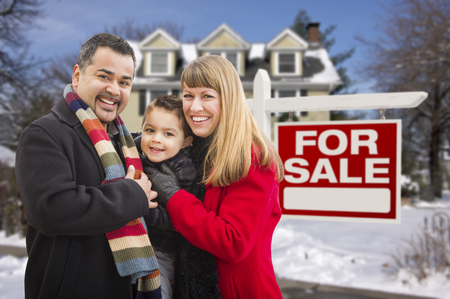 Warmly Dressed Young Mixed Race Family in Front of Home For Sale Real Estate Sign and House with Snow On The Ground. Stock Photo